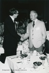 Bridgewater College, Pasco M. Bowman II (left) winner of a Distinguished Alumnus Award shakes hands with C. E. May, 1984 by Bridgewater College