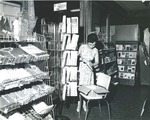 Bridgewater College, Employee arranging card rack at campus store, undated by Bridgewater College