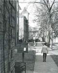 Bridgewater College, Students walking on sidewalk in front of Founders' Hall with bulletin box visible, maybe 1970s by Bridgewater College