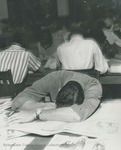Bridgewater College, Student sleeping on newspaper in BC library in Cole Hall basement, undated by Bridgewater College