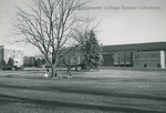 Bridgewater College, Students under a bare tree on the campus mall with Kline Campus Center and Rebecca Hall in the background, undated by Bridgewater College