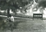Bridgewater College, Student reading on lawn near Alexander Mack Memorial Library sign, circa 1973 by Bridgewater College