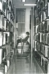 Bridgewater College, Through stacks of a student studying in a carrel at the Alexander Mack Memorial Library, undated by Bridgewater College