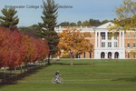 Bridgewater College, Autumn scene of a student riding a bicycle in front of the McKinney Center, undated by Bridgewater College