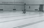 Bridgewater College, A student squats and touches the water in the Nininger Hall swimming pool, September 1980 by Bridgewater College