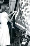 Bridgewater College, Student worker pinning a label on a quilt in the Reuel B. Pritchett Museum, undated by Bridgewater College