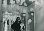 Bridgewater College, A student walks down a residence hall decorated with paper snowflakes, undated by Bridgewater College